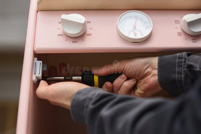 Carpinteiro no trabalho que faz o forno da cozinha do jogo Fechamento magnético de fixação com chave de fenda imagens de stock