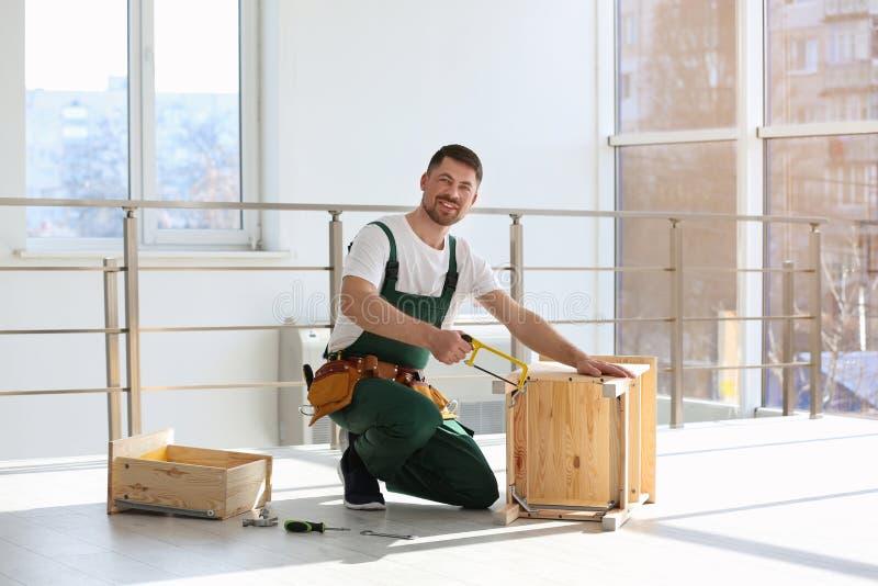 Carpinteiro no uniforme que faz a mobília Ferramentas profissionais da constru??o fotografia de stock