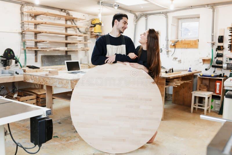 Carpinteiro novo na oficina do carpinteiro O homem guarda uma placa redonda de madeira para o texto Copyspace especialista novo,  imagens de stock