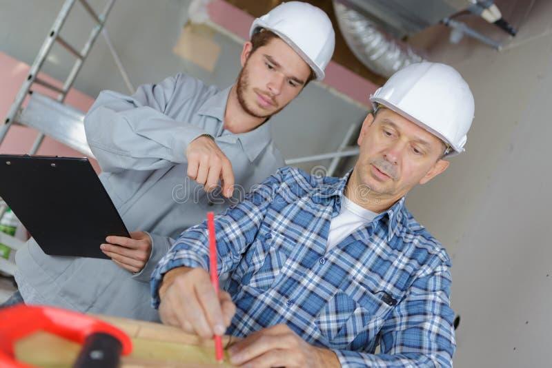 Carpinteiro novo que ajuda à placa de madeira de medição superior foto de stock royalty free