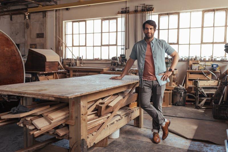 Carpinteiro novo que está por uma tabela em sua loja do woodworking imagem de stock