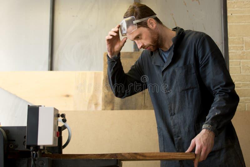 Carpinteiro novo que trabalha na serração na máquina-instrumento foto de stock royalty free