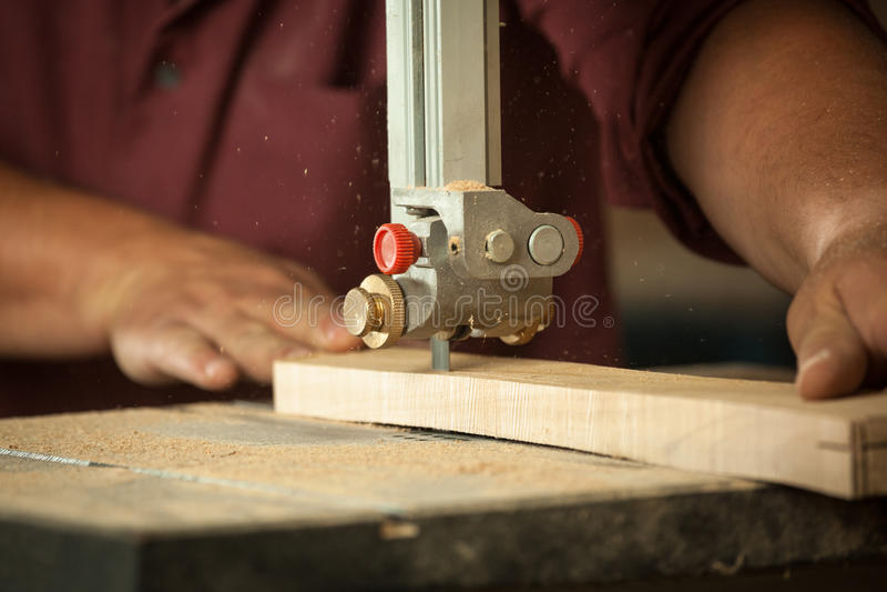 Carpinteiro profissional que trabalha com a máquina de sawing na oficina fotografia de stock