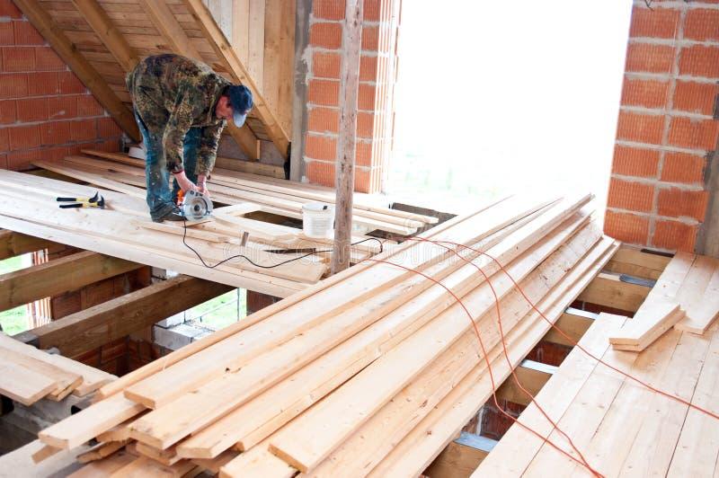 Carpinteiro que constrói o assoalho novo foto de stock
