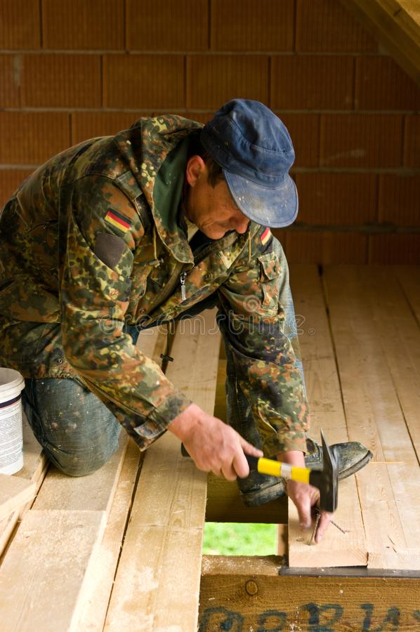 Carpinteiro que constrói o assoalho novo de uma sala do sótão fotografia de stock