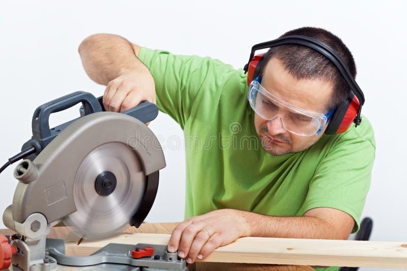 Carpinteiro que corta a prancha de madeira fotografia de stock royalty free