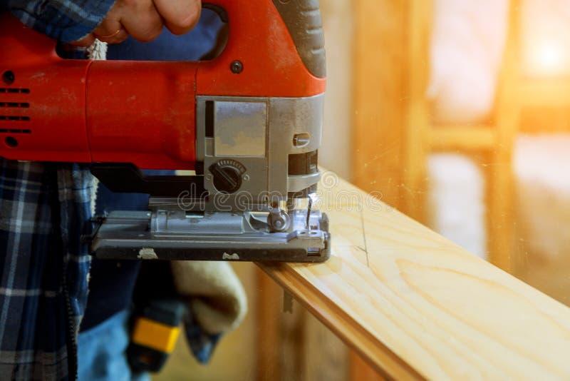 Carpinteiro que corta um painel de madeira com a serra de vaivém, ferramentas da carpintaria fotos de stock