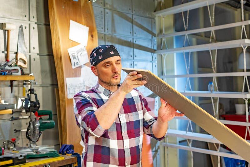 Carpinteiro que faz seu trabalho na oficina da carpintaria um homem em uma oficina da carpintaria mede e na estratificação dos co foto de stock royalty free