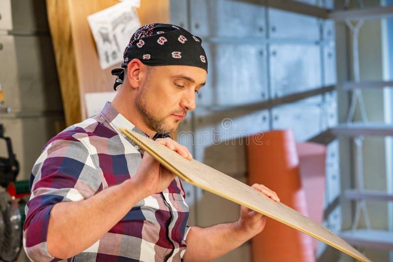 Carpinteiro que faz seu trabalho na oficina da carpintaria um homem em uma oficina da carpintaria mede e na estratificação dos co imagem de stock