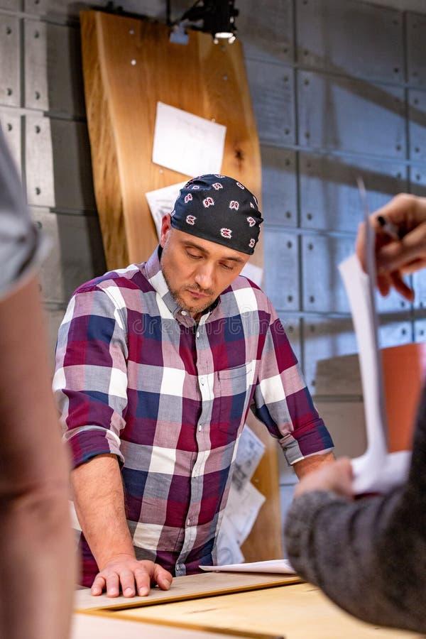 Carpinteiro que faz seu trabalho na oficina da carpintaria um homem em uma oficina da carpintaria mede e na estratificação dos co imagens de stock
