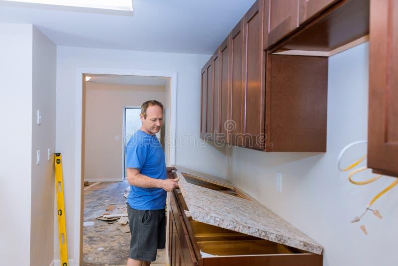 Carpinteiro que instala a parte superior contrária de c em uma cozinha foto de stock