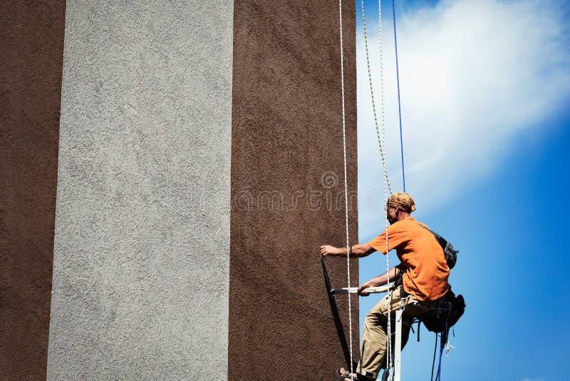 Carpinteiro que pinta uma tapeçaria larga da construção alta imagem de stock
