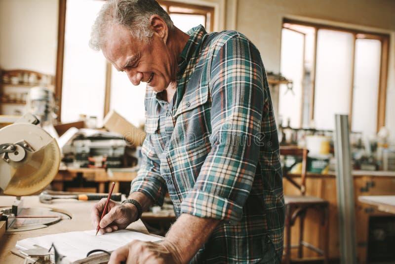 Carpinteiro que prepara o desenho para as peças da mobília imagem de stock