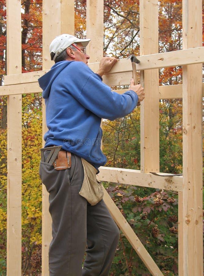 Carpinteiro que quadro a parede exterior da casa imagem de stock royalty free