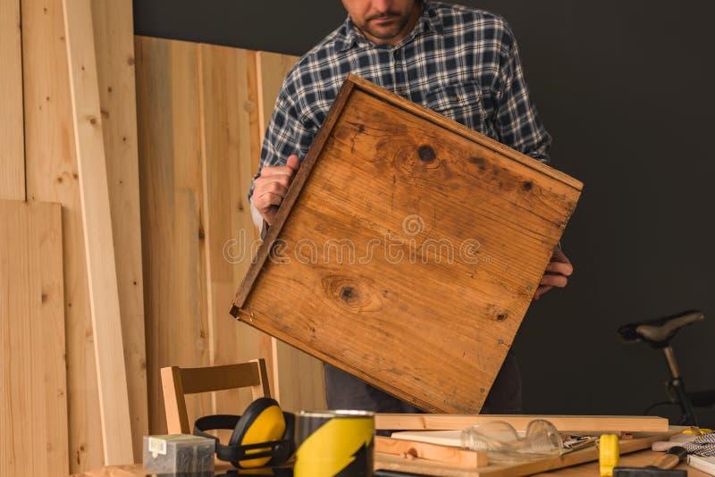Carpinteiro que repara a gaveta de madeira na oficina da carpintaria fotografia de stock royalty free