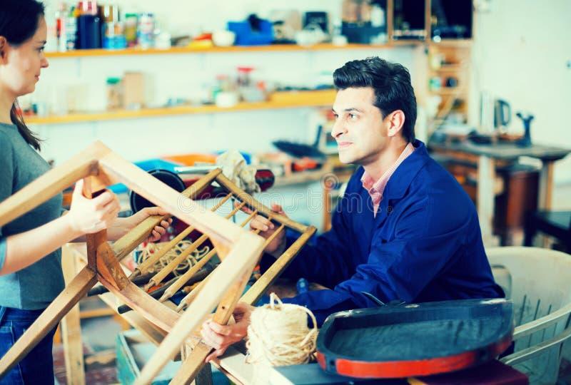 Carpinteiro que toma a cadeira para reparar imagens de stock royalty free