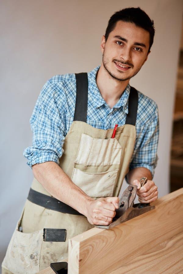 Carpinteiro que trabalha com madeira usando o plano contra a parede branca no estúdio foto de stock