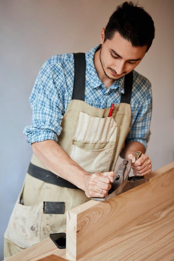 Carpinteiro que trabalha com madeira usando o plano contra a parede branca no estúdio fotografia de stock royalty free
