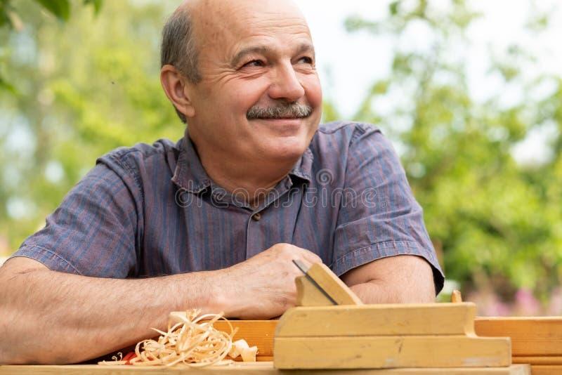 Carpinteiro que trabalha com plano no fundo de madeira imagem de stock
