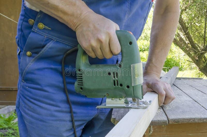Carpinteiro que trabalha com uma serra de vaiv?m el?trica O homem está vendo uma folha da madeira compensada com a máquina elétri foto de stock