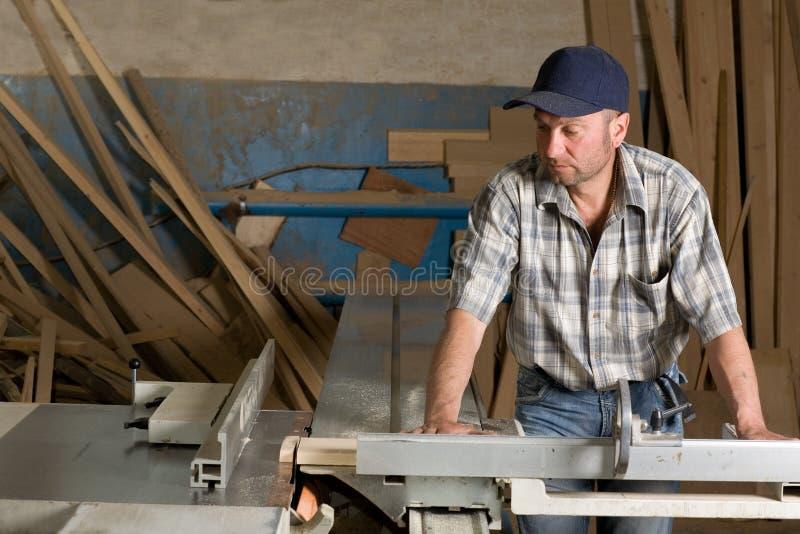 Carpinteiro que trabalha em máquinas do woodworking imagens de stock