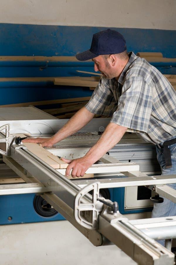 Carpinteiro que trabalha em máquinas do woodworking foto de stock royalty free