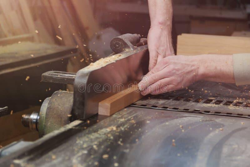 Carpinteiro que trabalha em máquinas do woodworking na loja da carpintaria Fim masculino da mão acima fotos de stock royalty free
