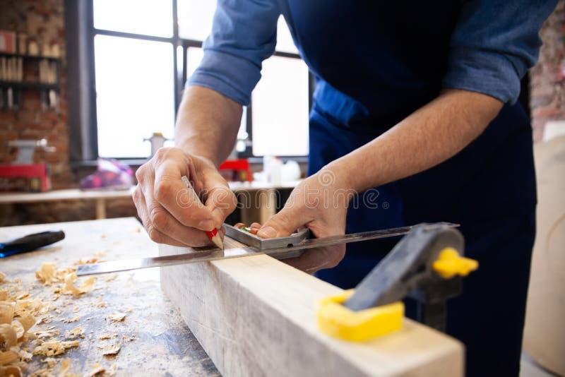 Carpinteiro que trabalha em m?quinas do woodworking na loja da carpintaria Um homem trabalha em uma loja da carpintaria imagem de stock royalty free