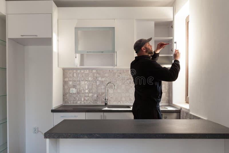 Carpinteiro que trabalha na cozinha nova Trabalhador manual que fixa uma porta em uma cozinha imagem de stock