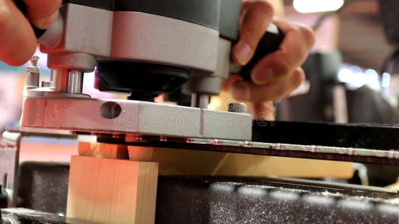 Carpinteiro que usa a ferramenta elétrica para o corte de forma vídeos de arquivo