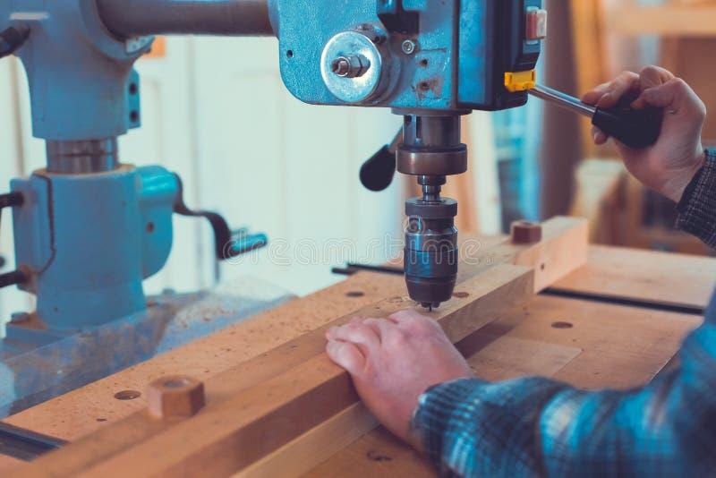 Carpinteiro que usa a imprensa de broca ao furo dos mae na prancha de madeira fotografia de stock royalty free