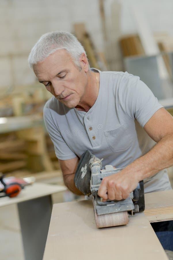 Carpinteiro que usa a máquina de lixar da correia imagens de stock