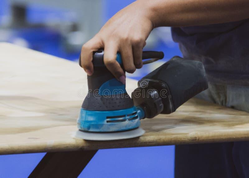 Carpinteiro que usa a máquina de lixar para a tabela de madeira fotos de stock
