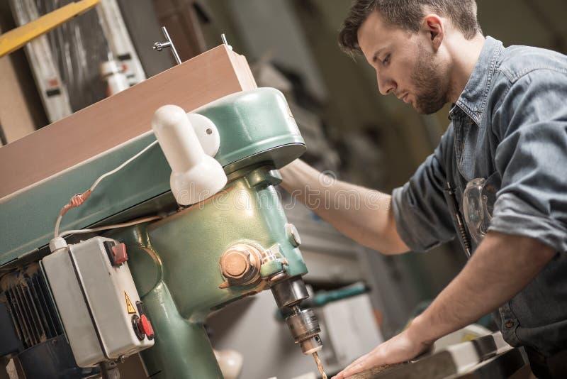 Carpinteiro que usa a máquina de sawing foto de stock