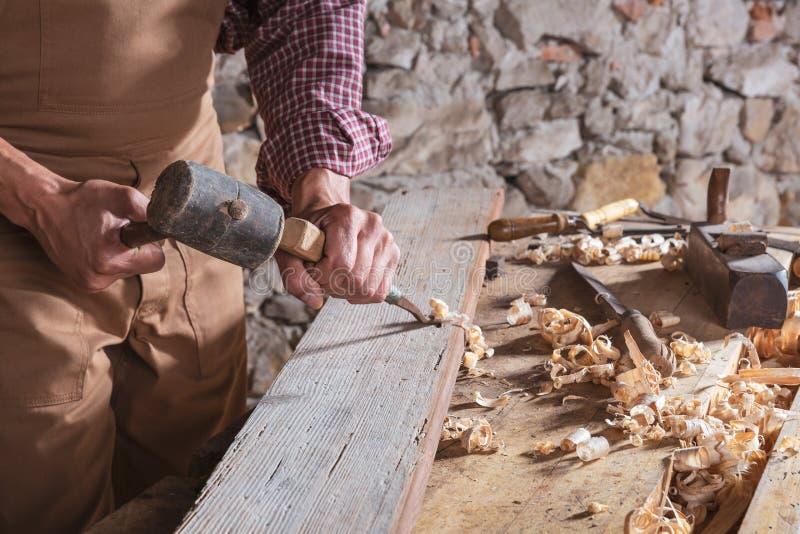 Carpinteiro que usa o formão para alisar abaixo da madeira foto de stock royalty free