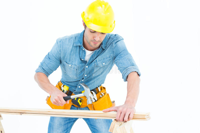 Carpinteiro que usa o martelo na madeira fotografia de stock