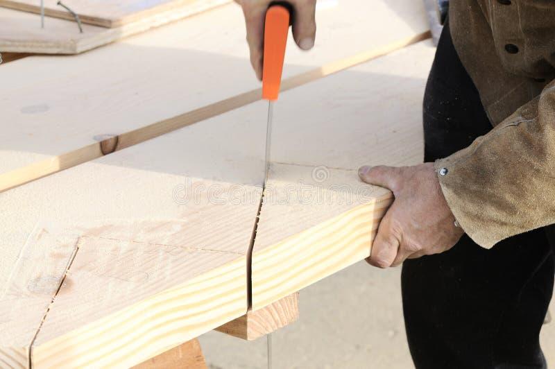 Carpinteiro que usa a serra da mão fotos de stock