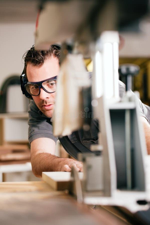 Carpinteiro que usa a serra elétrica fotografia de stock royalty free