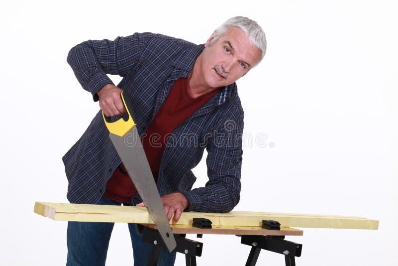 Carpinteiro que usa um handsaw imagem de stock royalty free