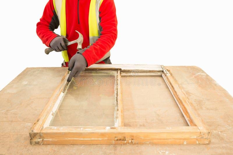 Carpinteiro que usa um martelo ao reparar uma faixa velha do quadro de janela foto de stock