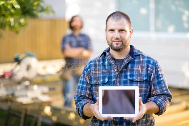 Carpinteiro seguro Displaying Digital Tablet com imagens de stock royalty free