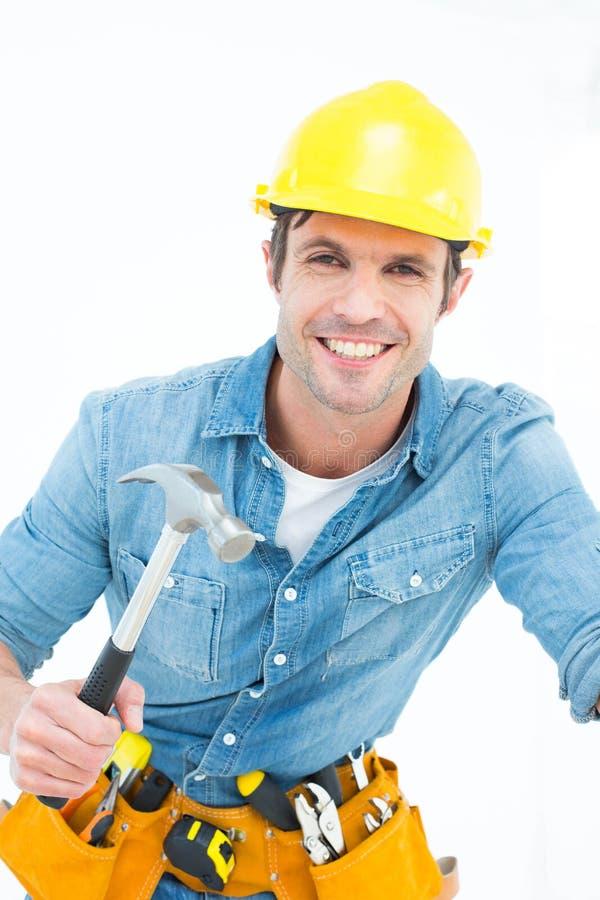 Carpinteiro seguro que usa o martelo foto de stock