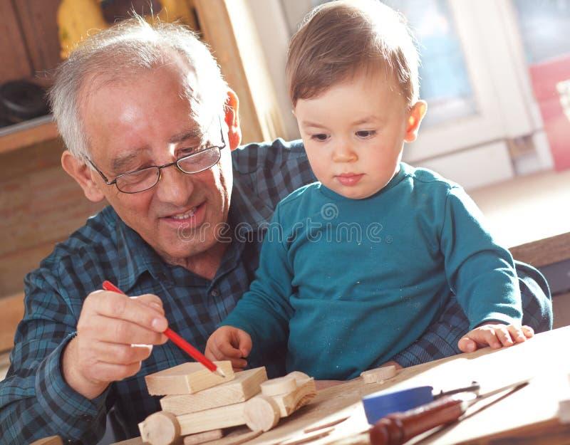 Carpinteiro superior e seu neto fotografia de stock royalty free