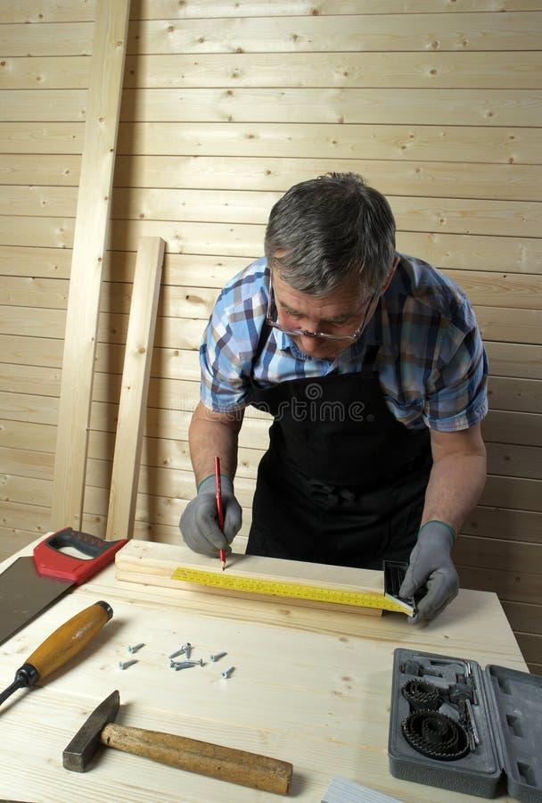 Carpinteiro superior que trabalha em sua oficina imagens de stock royalty free