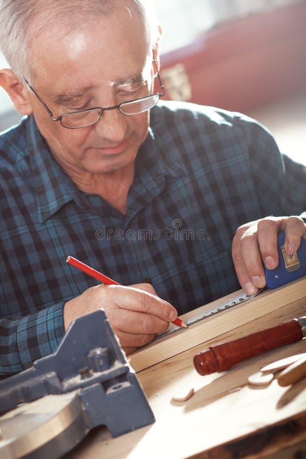 Carpinteiro superior que trabalha olá! na oficina fotografia de stock