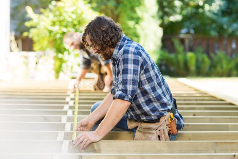 Carpinteiros adultos meados de que medem a madeira com fita fotos de stock royalty free