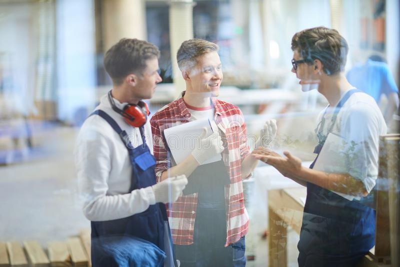 Carpinteiros novos positivos que discutem o primeiro projeto imagens de stock royalty free