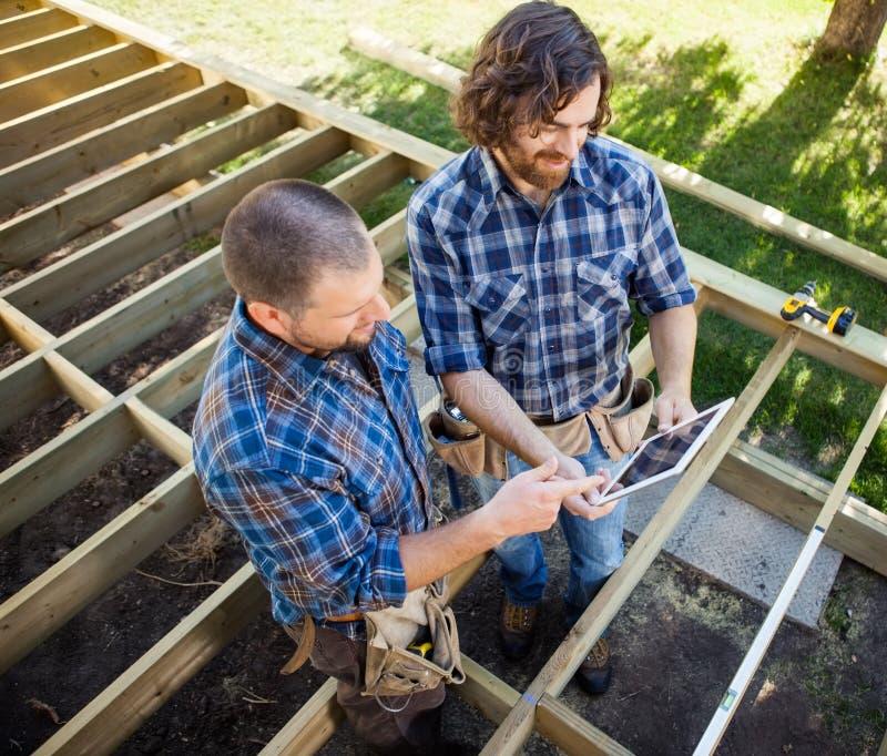 Carpinteiros que discutem o projeto na tabuleta de Digitas imagens de stock