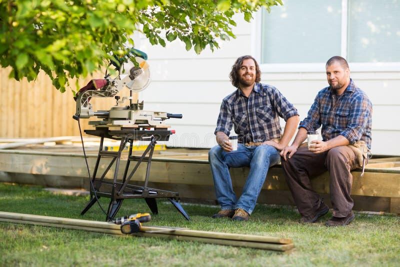 Carpinteiros que guardam copos descartáveis ao sentar-se fotografia de stock