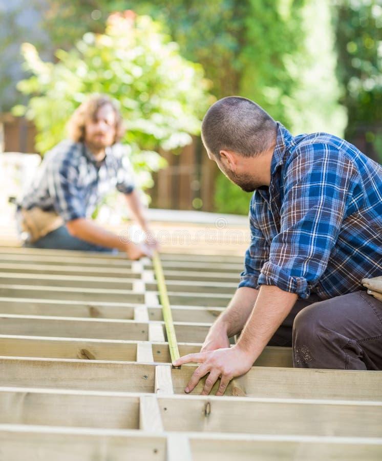 Carpinteiros que medem a madeira com a fita no local imagens de stock royalty free